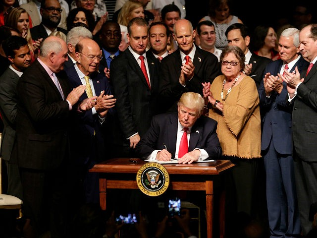 President Donald Trump signs an executive order on a revised Cuba policy aimed at stopping the flow of U.S. cash to the country's military and security services while maintaining diplomatic relations, Friday, June 16, 2017, in Miami. From left are, Agriculture Secretary Sonny Perdue, Commerce Secretary Wilbur Ross, Rep. Mario Diaz-Balart, R-Fla., Florida Gov. Rick Scott, Cary Roque, Vice President Mike Pence and Labor Secretary Alex Acosta. (AP Photo/Lynne Sladky)