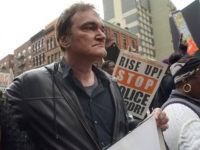 """FILE - In this Oct. 24, 2015 file photo, director Quentin Tarantino, center, participates in a rally to protest against police brutality in New York. Speakers at the protest said they want to bring justice for those who were killed by police. Tarantino's new film, """"The Hateful Eight,"""" opens in U.S. theaters on Jan. 1, 2016. (AP Photo/Patrick Sison, File"""