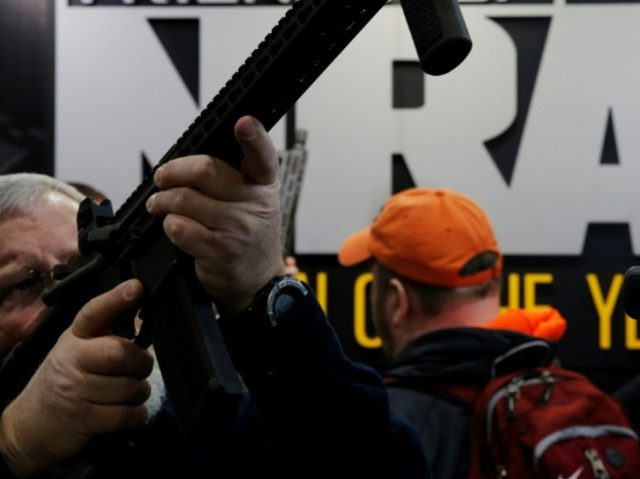 A visitor sights a rifle at a National Rifle Association outdoor sports trade show. The NRA backs Wisconsin's new law allowing children younger than 10 to carry firearms in the forest