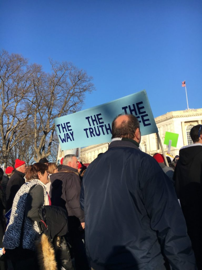 March for Life on January 19, 2018. Marchers carry a sign that reads,