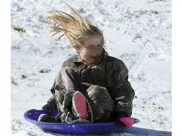 Blythe Kiser, 8, enjoys a ride on a saucer sled Thursday, Jan. 18, 2018, at Nash Community College in Rocky Mount, N.C. snowfall (Alan Campbell/The Rocky Mount Telegram via AP)
