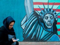 TEHRAN, IRAN - DECEMBER 20: Woman with phone passing in front of an anti-american propoganda slogan depicting statue liberty skeleton on the wall of the united states embassy, central district, tehran, Iran on December 20, 2015 in Tehran, Iran. (Photo by Eric Lafforgue/Art in All of Us/Corbis via Getty Images)