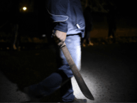 A hooded man carrying a machete patrols the streets in the village of 'Lo de Reyes', in the municipality of San Pedro Ayampuc, 20 km north of Guatemala City on March 2, 2017, to prevent attacks from gang members. The residents 'Lo de Reyes' were organized to defend themselves against criminals and stalking by members of the gangs 'Salvatrucha' and 'Barrio 18'. Guatemala, along with neighboring El Salvador and Honduras, suffers rampant violence, much of it linked to criminal gangs. Some 6,000 people a year are murdered in the country. / AFP PHOTO / Johan ORDONEZ (Photo credit should read JOHAN ORDONEZ/AFP/Getty Images)