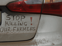 A bumper sign during a blockade of the freeway between Johannesburg and Vereeniging, in Midvaal, South Africa, in protest against the recent murder of farmers, Monday, Oct 30 2017. Traffic was bought to a standstill on highways leading from farming areas to Cape Town, Pretoria and Johannesburg, as white farmers protest in what they call the Black Monday protest against the high rate of murders of farmer workers. (AP Photo/Themba Hadebe)