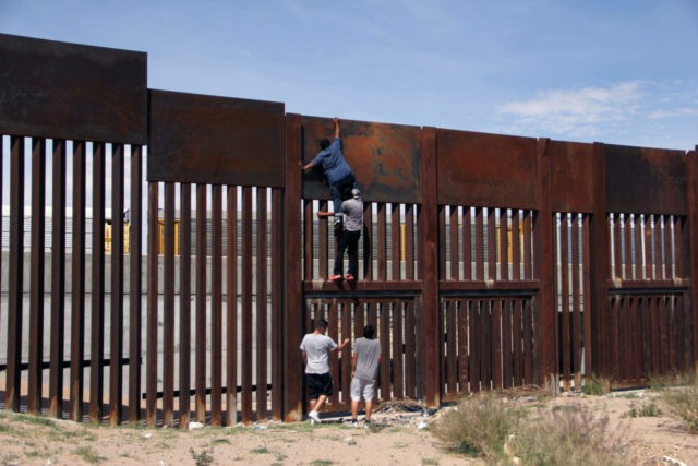 A young Mexican helps a compatriot to climb the metal wall that divides the border between Mexico and the United States to cross illegally to Sunland Park, from Ciudad Juarez, Chihuahua state, Mexico on April 6, 2018. US President Donald Trump on April 5, 2018, said he would send thousands …