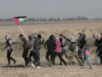 Palestinian masked protesters carrying tires walk toward the border fence during clashes with Israeli troops along Gaza's border with Israel, east of Khan Younis, Gaza Strip, Thursday, April 5, 2018. An Israeli airstrike in northern Gaza early on Thursday killed a Palestinian, while a second man died from wounds sustained in last week's mass protest. The fatalities bring to 21 the number of people killed in confrontations in the volatile area over the past week with a new round of protests along the border is expected on Friday. (AP Photo/Adel Hana)