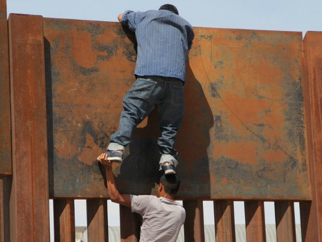 A young Mexican helps a compatriot to climb the metal wall that divides the border between Mexico and the United States to cross illegally to Sunland Park, from Ciudad Juarez, Chihuahua state, Mexico on April 6, 2018. US President Donald Trump on April 5, 2018 said he would send thousands of National Guard troops to the southern border, amid a widening spat with his Mexican counterpart Enrique Pena Nieto. The anti-immigration president said the National Guard deployment would range from 2,000 to 4,000 troops, and he would 'probably' keep many personnel on the border until his wall is built -- spelling out a lengthy mission. / AFP PHOTO / HERIKA MARTINEZ (Photo credit should read HERIKA MARTINEZ/AFP/Getty Images)