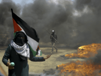 A woman holds a Palestinian flag as a protester burns tires near the Israeli border fence, east of Khan Younis, in the Gaza Strip, Monday, May 14, 2018. Thousands of Palestinians are protesting near Gaza's border with Israel, as Israel prepared for the festive inauguration of a new U.S. Embassy in contested Jerusalem. (AP Photo/Adel Hana)