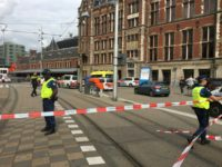 Security officials cordon off an area outside the Central Railway Station in Amsterdam following an attack by a knife-wielding man who wounded two American tourists.