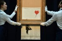 British street artist Banksy created an art world sensation by sending his painting through a shredder hidden in a frame moments after it sold at auction for £1,042,000 ($1.4 million, 1.2 million euros)