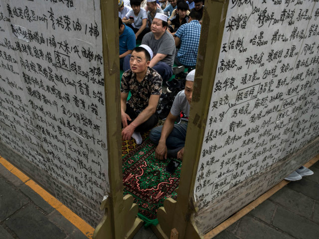 Chinese Hui Muslim men wait on a carpet before Eid al-Fitr prayers marking the end of the holy fasting month of Ramadan at the historic Niujie Mosque on June 16, 2018 in Beijing, China. Islam in China dates back to the 10th century as the legacy of Arab traders who …