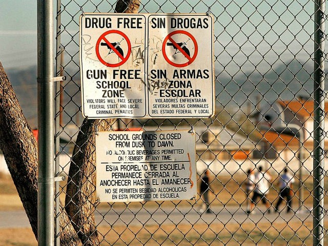 Drug and gun free school zone signs are shown as students play basketball at an elementary school Tuesday, Dec. 14, 2004, in Phoenix. Parents trying to get reports on violence and drugs at their kid's schools stand a good chance of having their intentions examined when they ask for public …