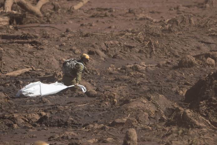 An Israeli rescue specialist drags an empty bag as he walks in the mud as he arrives at a site where a body was found inside a vehicle stuck in the mud, days after a dam collapse in Brumadinho, Brazil, Monday, Jan. 28, 2019. Firefighters on Monday carefully moved over treacherous mud, sometimes walking, sometimes crawling, in search of survivors or bodies four days after a dam collapse that buried mine buildings and surrounding neighborhoods with iron ore waste. (AP Photo/Leo Correa)
