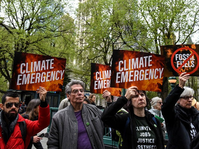 """NEW YORK, NY - APRIL 17: People hold sign saying """"climate emergency"""" while participating in a direct action with a protest group called Extinction Rebellion on April 17, 2019 in New York City. The activists are demanding governments declare a climate emergency to combat pollution. (Photo by Stephanie Keith/Getty Images)"""