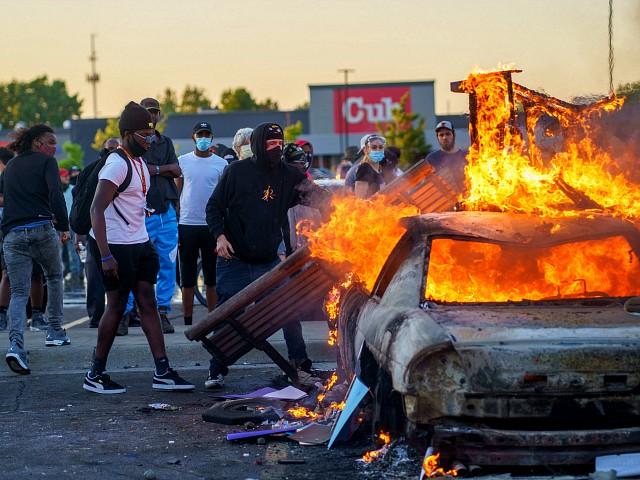 Protesters throw objects onto a burning car outside a Target store near the Third Police Precinct on May 28, 2020 in Minneapolis, Minnesota, during a demonstration over the death of George Floyd, an unarmed black man, who died after a police officer kneeled on his neck for several minutes. - Authorities in Minneapolis and its sister city St. Paul got reinforcements from the National Guard on May 28 as they girded for fresh protests and violence over the shocking police killing of a handcuffed black man. Three days after a policeman was filmed holding his knee to George Floyd's neck for more than five minutes until he went limp, outrage continued to spread over the latest example of police mistreatment of African Americans. protest (Photo by kerem yucel / AFP) (Photo by KEREM YUCEL/AFP via Getty Images)