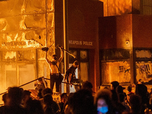 TOPSHOT - Flames from a nearby fire illuminate protesters standing on a barricade in front of the Third Police Precinct on May 28, 2020 in Minneapolis, Minnesota, during a protest over the death of George Floyd, an unarmed black man, who died after a police officer kneeled on his neck for several minutes. - A police precinct in Minnesota went up in flames late on May 28 in a third day of demonstrations as the so-called Twin Cities of Minneapolis and St. Paul seethed over the shocking police killing of a handcuffed black man. The precinct, which police had abandoned, burned after a group of protesters pushed through barriers around the building, breaking windows and chanting slogans. A much larger crowd demonstrated as the building went up in flames. (Photo by kerem yucel / AFP) (Photo by KEREM YUCEL/AFP via Getty Images)