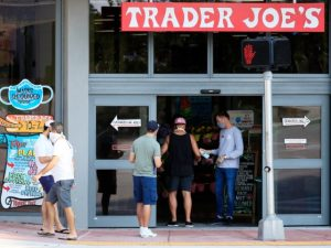 MIAMI BEACH, FL - APRIL 14: A store associate distributes hand sanitizer to customers as they enter the Trader Joe's store in South Beach on April 14, 2020 in Miami Beach, Florida. The city of Miami Beach put in place an emergency measure requiring all customers and employees at grocery …