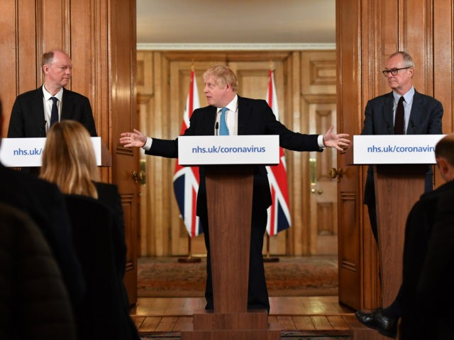 LONDON, ENGLAND - MARCH 19: Chief Medical Officer Professor Chris Whitty (L) and Chief Scientific Adviser Patrick Vallance (R) look on as British Prime Minister Boris Johnson (C) gestures as he speaks during a coronavirus news conference inside number 10 Downing Street on March 19, 2020 in London, England. Coronavirus …