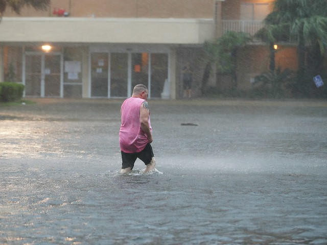 GULF SHORES, ALABAMA - SEPTEMBER 15: A man walks though a flooded parking lot as the outer bands of Hurricane Sally come ashore on September 15, 2020 in Gulf Shores, Alabama. The storm is bringing heavy rain, high winds and a dangerous storm surge from Louisiana to Florida. (Photo by Joe Raedle/Getty Images)