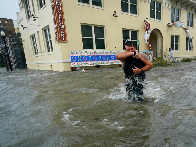Trent Airhart wades through floodwaters, Wednesday, Sept. 16, 2020, in downtown Pensacola, Fla. Hurricane Sally made landfall Wednesday near Gulf Shores, Alabama, as a Category 2 storm, pushing a surge of ocean water onto the coast and dumping torrential rain that forecasters said would cause dangerous flooding from the Florida Panhandle to Mississippi and well inland in the days ahead.(AP Photo/Gerald Herbert)