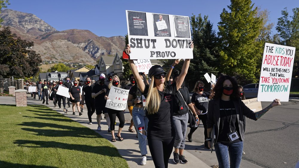 Paris Hilton, center, leads a protest Friday, Oct. 9, 2020, in Provo, Utah. Hilton was in Utah Friday to lead a protest outside a boarding school where she alleges she was abused physically and mentally by staff when she was a teenager. Hilton, now 39, went public with the allegations in a new documentary and wants a school that she says left her with nightmares and insomnia for years to be shut down. (AP Photo/Rick Bowmer)