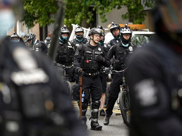 Seattle Police prepare to move in on demonstrators blocking the intersection of East Pine Street and 11th Avenue after the Capitol Hill Occupied Protest (CHOP) was cleared out and police retook the department's East Precinct in Seattle, Washington on July 1, 2020. (Photo by Jason Redmond / AFP) (Photo by …