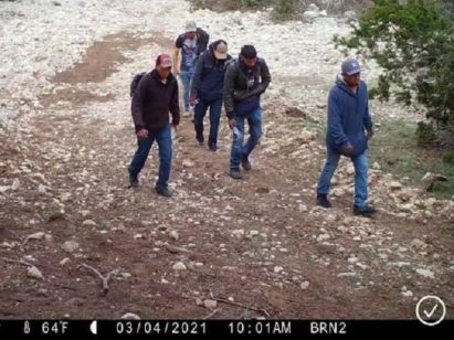 A rancher's game-cam captures a group of migrants marching through his ranch to avoid a Border Patrol checkpoint. (Photos: Kinney County Sheriff's Office)