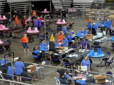 FILE - In this May 6, 2021 file photo, Maricopa County ballots cast in the 2020 general election are examined and recounted by contractors working for Florida-based company, Cyber Ninjas at Veterans Memorial Coliseum in Phoenix. For some conspiracy theorists, the 2020 election still hasn't ended. Trump supporters are pushing …