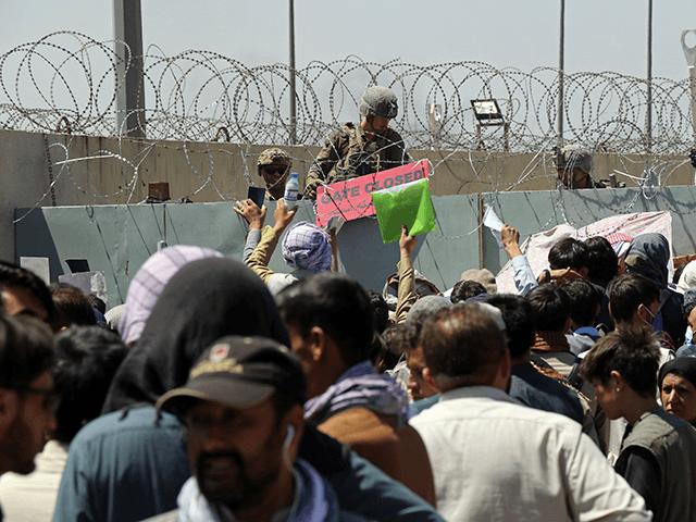 Ein US-Soldat hält ein Schild, das darauf hinweist, dass ein Tor geschlossen ist, während Hunderte von Menschen einige Dokumente sammeln, die sich in der Nähe eines Evakuierungskontrollpunkts am Rande des internationalen Flughafens Hamid Karzai in Kabul, Afghanistan, am Donnerstag, 26. August 2021, befinden. Westliche Nationen warnte am Donnerstag vor einem möglichen Angriff auf den Flughafen von Kabul, auf den Tausende strömten, um in den nachlassenden Tagen einer massiven Luftbrücke aus dem von den Taliban kontrollierten Afghanistan zu fliehen. Großbritannien sagte, ein Angriff könne innerhalb von Stunden erfolgen. (AP-Foto/Wali Sabawoon)