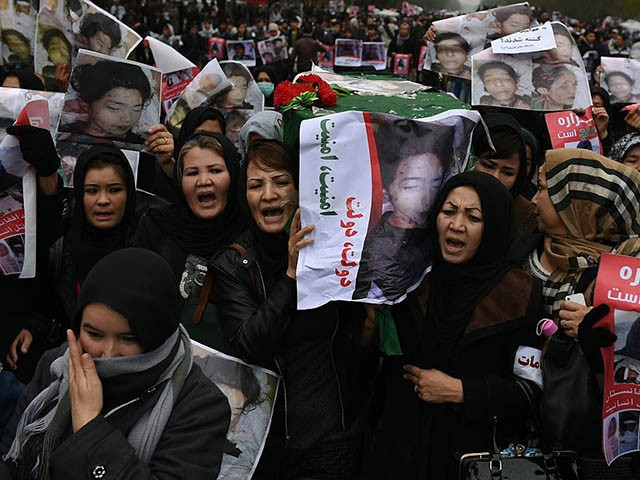 Afghan protesters carry a coffin containing a decapitated body of one of seven Shiite Muslim Hazaras, including four men, two women and one child, during a demonstration in Kabul on November 11, 2015. Thousands of protesters marched coffins containing the decapitated bodies of seven Shiite Hazaras through the Afghan capital Kabul on November 11 to demand justice for the gruesome beheadings, which prompted fears of sectarian bloodshed in the war-torn country. Demonstrators gathered in the rain in west Kabul and marched towards the city centre, chanting death slogans to the Taliban and the Islamic State group while demanding justice and protection from the government. AFP PHOTO / SHAH Marai (Photo credit should read SHAH MARAI/AFP via Getty Images)