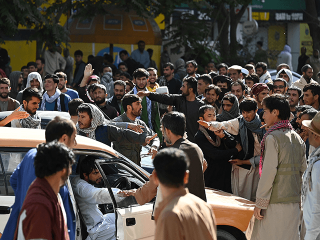 Bank account holders gather outside a closed bank building in Kabul on August 28, 2021, following the Taliban's stunning military takeover of Afghanistan. - Since the Taliban seized power 14 days ago government buildings, banks, schools and universities have remained largely closed. (Photo by Aamir QURESHI / AFP) (Photo by AAMIR QURESHI/AFP via Getty Images)
