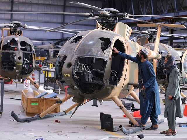 Taliban fighters check the cockpit of a damaged Afghan Air Force helicopter at a hangar at the airport in Kabul on September 14, 2021. (Karim Sahib/AFP via Getty Images)