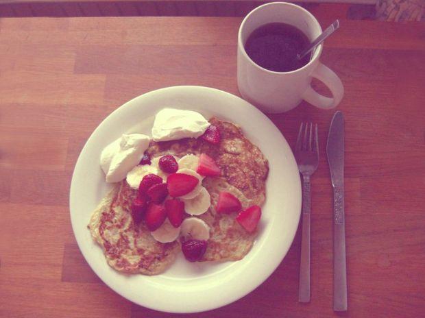 Ägg- och bananpannkakor med skivade jordgubbar och banan med några klickar naturell kvarg, en kopp te