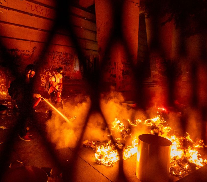 A protester extinguishes a fire set by fellow protesters at the Mark O. Hatfield United States Courthouse on Wednesday, July 22, 2020, in Portland, Ore. (AP Photo/Noah Berger)