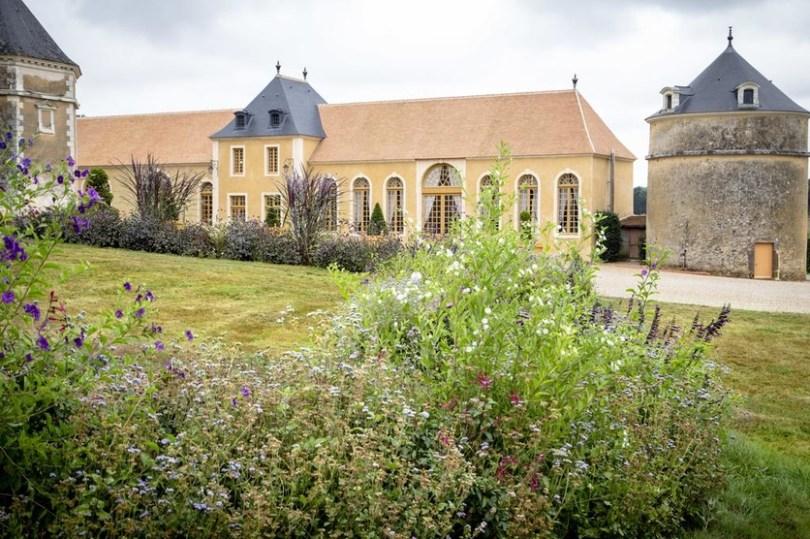 le château de la Groirie et sa propriétaire depuis les jardins fleuris