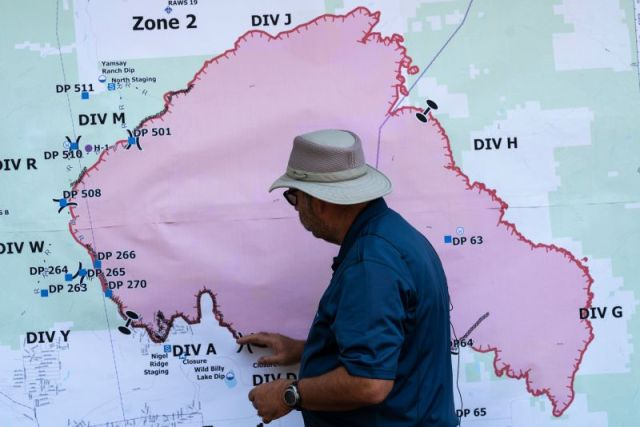 Operations Section Chief Bert Thayer examines a map of the Bootleg Fire in Chiloquin, Oregon, on July 13.
