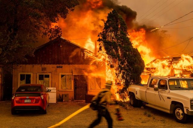 Fire consumes a home as the Sugar Fire, part of the Beckwourth Complex Fire, tears through Doyle, California, on July 10. It's the <a href=