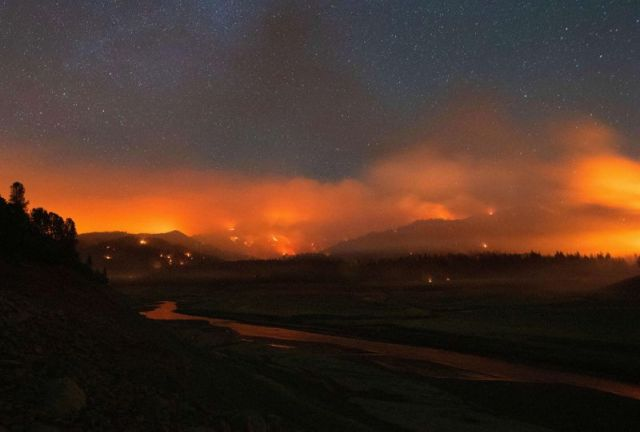 In this long-exposure photograph, taken early on July 2, flames surround a drought-stricken Shasta Lake during the Salt Fire in Lakehead, California.
