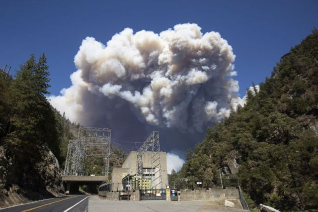 Plumes of smoke from the Dixie Fire rise above California's Plumas National Forest, near the Pacific Gas and Electric Rock Creek Power House, on July 21.