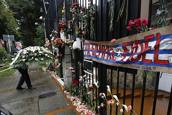 A man delivers a funeral wreath to the Cuban Embassy as a tribute for the late Cuban leader Fidel Castro, in Bogota, Colombia, Monday, Nov. 28, 2016. Castro, who led a rebel army to improbable victory, embraced Soviet-style communism and defied the power of 10 U.S. presidents during his half century rule of Cuba, died Friday at age 90. (AP Photo/Fernando Vergara)