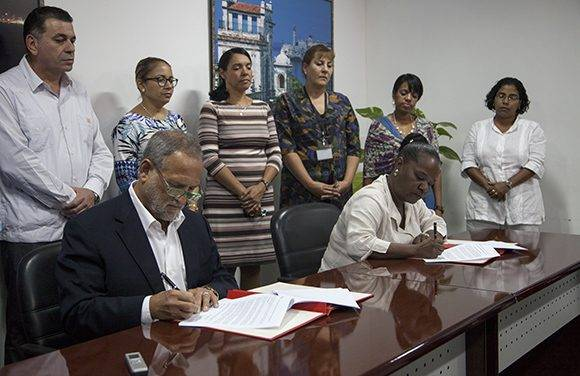 Scott Gilbert, presidente de la empresa estadounidense Coabana Trading LLC e Isabel O'Reilly, directora de CubaExport, firman el acuerdo que permite la exportación de carbón vegetal cubano a los Estados Unidos. Foto: Ladyrene Pérez/ Cubadebate.
