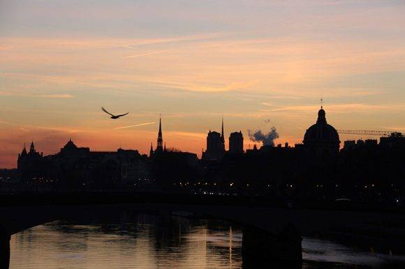A picture taken on January 6, 2017 in Paris shows the sunrise above Notre Dame de Paris cathedral and the Institut de France. / AFP PHOTO / LUDOVIC MARIN