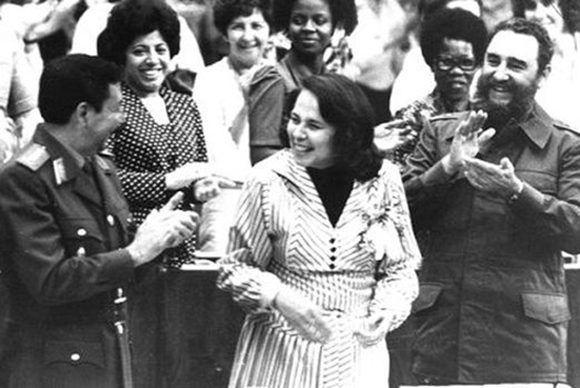 Fidel participa en la clausura del III Congreso de la Federación de Mujeres Cubanas, a su lado Vilma Espín Guillois, Secretaria de la FMC y el General de Ejército Raúl Castro Ruz, 8 de marzo de 1980. Foto tomada de Fidel Soldado de las Ideas.