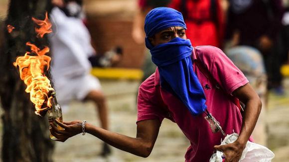 """Un opositor """"pacífico"""" lanza un cóctel molotov durante una protesta en Caracas, el 20 de julio de 2017. Foto: Ronaldo Schemidt / AFP/Getty Images."""