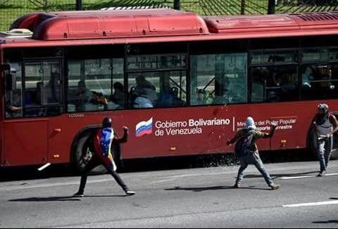 Un grupo de adolescentes lanzan cócteles molotov y piedras contra un bus en Caracas. Foto: Twitter