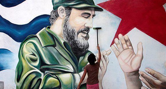 Un garçon peint une fresque dédiée à Fidel. Photo: Oswaldo Rivas / Reuters.