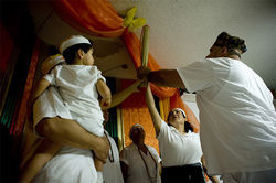 Inside Jose Merced's shrine room, devotees of all ages participate in the cleansing ceremony for Virginia Rosario-Nevarez as part of her seven-day initiation into the Santería priesthood.