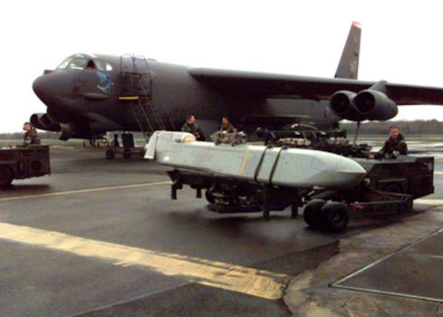 A U.S. Air Force airman transports an AGM-86C Conventional Air Launched Cruise Missile (CALCM) to a waiting a B-52H Stratofortress at RAF Fairford, United Kingdom, on March 30, 1999. The Stratofortress is being prepared for a mission in support of NATO Operation Allied Force, which is the air operation against targets in the Federal Republic of Yugoslavia. The Stratofortress and its crew are deployed from the 2nd Bomb Wing, Barksdale Air Force Base, La.