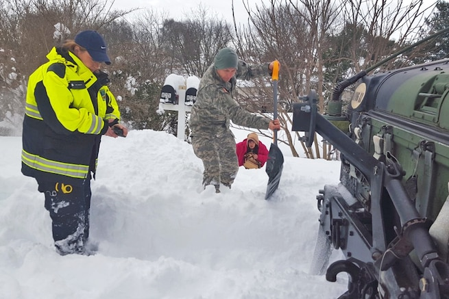 A soldier helps clear a path while assisting the Waynesboro First Aid Crew with a rescue call near Waynesboro, Va., Jan. 23, 2016. The soldier is with the Virginia National Guard's Company D, 1st Battalion, 116th Infantry Regiment, 116th Infantry Brigade Combat Team. The first aid crew members were unable to reach the location of the call with their ambulance, so soldiers drove them to the residence, cleared a path and transported the patient to the ambulance for evacuation. Virginia National Guard photo by Army Sgt. Chris Martrano