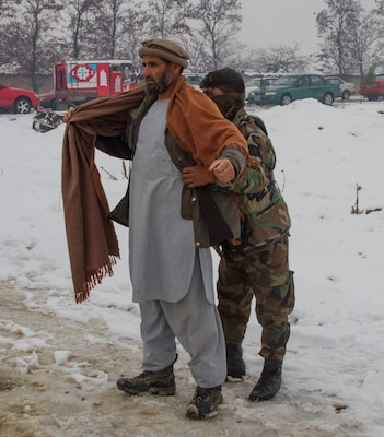 An Afghan soldier searches people receiving supplies in Afghanistan's Parwan province during a humanitarian aid mission, Jan. 28, 2017. Army photo by Sgt. 1st Class Eliodoro Molina